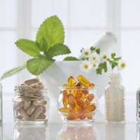 Herbal medicine pills and mortar over bright  background