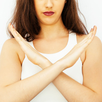 Beautiful young Caucasian woman saying no with crossed arms hands