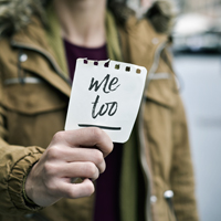 woman showing a note with the text me too