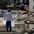 A local resident walks on submerged and destroyed houses in a flooded area in Mabi town in Kurashiki